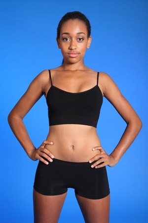 Fit athletic torso of beautiful healthy young african american woman wearing black sports underwear, standing against blue background showing off toned body. Stock Photo - 10763766