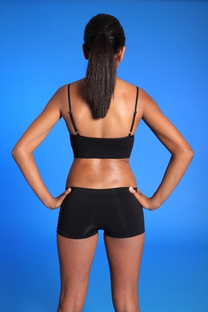 knickers: Rear torso view of a beautiful healthy young african american woman wearing black sports underwear, standing against blue background showing off fit body.