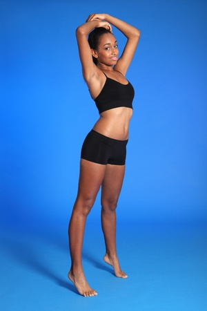 Athletic beautiful healthy young african american woman wearing black sports underwear, standing against blue background showing off fit body. photo