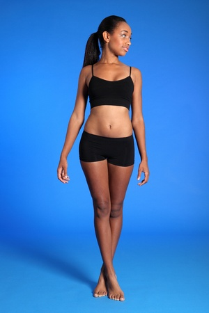 Happy smile from athletic beautiful young african american woman wearing black sports underwear, standing against blue background showing off fit healthy body. Stock Photo - 10763737