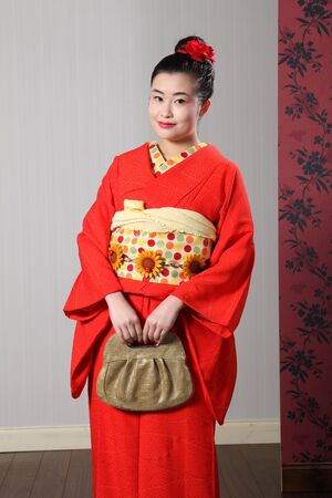 kanzashi: Beautiful young oriental woman wearing red Japanese traditional kimono, a full length robe garment complete with obi sash and fashion bag. Model wearing red kanzashi flower in hair. Stock Photo