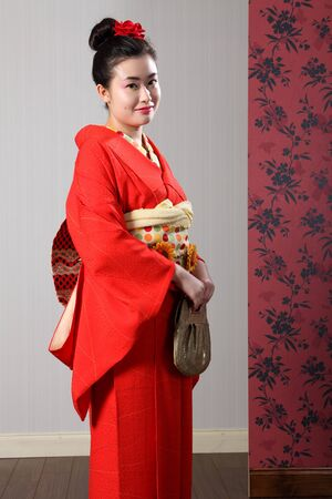 kanzashi: Kimono model beautiful young oriental woman wearing red Japanese traditional kimono, a full length robe garment complete with obi sash and fashion bag. Model wearing red kanzashi flower in hair.