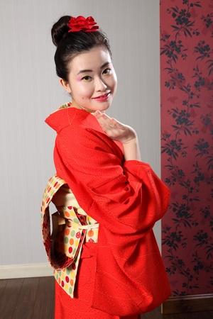 kanzashi: Greeting with a wave by Asian model beautiful young oriental woman wearing red Japanese traditional kimono, a full length robe complete with obi sash and red kanzashi flower in hair.