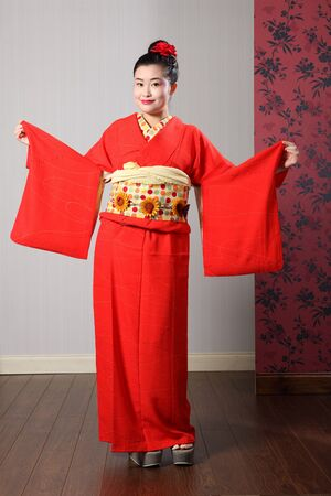 modelled: Large sleeves on traditional red Japanese kimono robe garment complete with obi sash being modelled by beautiful young asian oriental model with kanzashi hair flower.