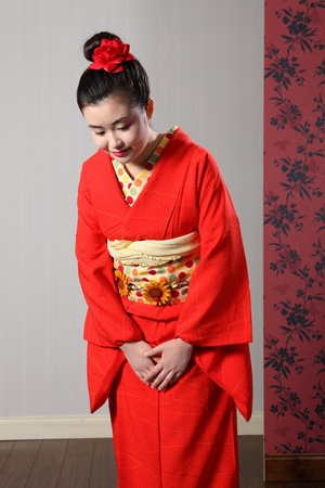 Respectful bow by beautiful young oriental model in red Japanese kimono robe garment complete with obi sash and kanzashi hair flower.