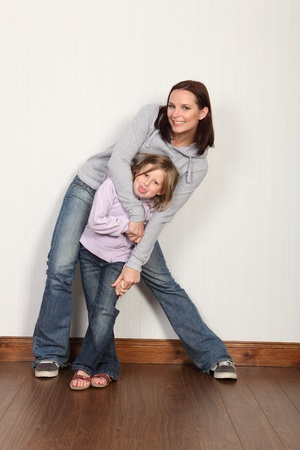 skirting: Happy young family of mum and daughter with hug and embrace with big laughing smiles. Both wearing denim jeans and hoodie.