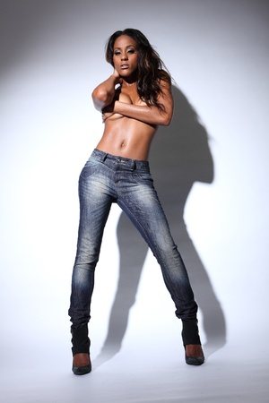 topless jeans: Sexy young african american woman modelling blue denim jeans, topless with hands covering her breasts and long dark hair.