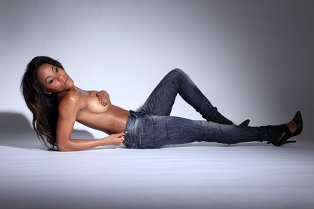 Lying on floor a semi naked sexy young african american woman modelling blue denim jeans, topless with hands covering her breasts and long dark brown hair. Stock Photo - 10782744