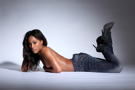 Stunning semi naked young african american woman modelling blue denim jeans, lying in a sexy pose on the floor topless with hands covering her breasts and long dark brown hair.