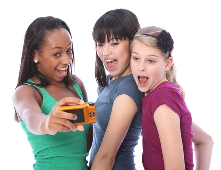 Fun photography with digital camera for three pretty young teenager girl friends a blonde caucasian, an oriental Japanese and an African American mixed race student all having a laugh together. photo