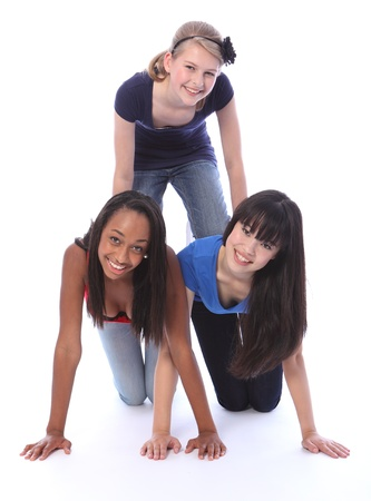 Human pyramid fun by three multi cultural teenage school student friends made up of mixed race african american, oriental Japanese and caucasian all with big smiles having a laugh. Stock Photo - 10782749