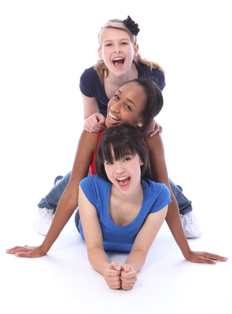 Human totem pole fun by three multi cultural teenage school student friends made up of mixed race african american, oriental Japanese and caucasian all with big smiles having a laugh.