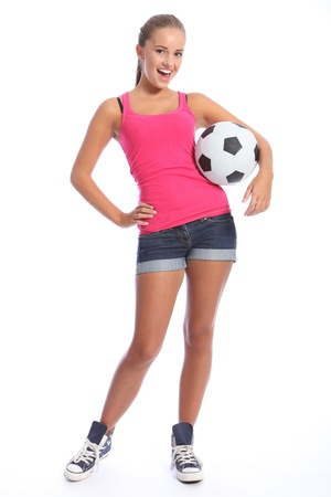 denim shorts: Beautiful soccer player teenage girl with happy smile wearing pink vest and denim shorts, standing with sports ball. Full length shot against white background. Stock Photo