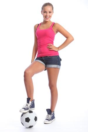 indoor soccer: Hermosa futbolista adolescente con sonrisa feliz vistiendo chaleco de color rosa y pantalones cortos de mezclilla, de pie con bola deportes. Longitud total de un disparo contra el fondo blanco.