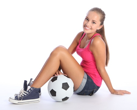 sixteen: Beautiful soccer player teenage girl with happy smile wearing pink vest and denim shorts, sitting on floor with sports ball. Full body shot against white background.