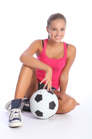 Fit young teenage athlete sitting on floor with soccer ball with beautiful smile wearing pink vest and denim shorts. Full body shot against white background.