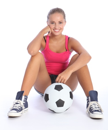 female soccer: Fit young teenage athlete sitting on floor with soccer ball with beautiful smile wearing pink vest and denim shorts. Full body shot against white background.