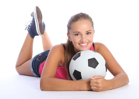 female soccer: Fit young teenage athlete girl lying on the floor holding soccer ball with beautiful smile wearing pink vest and denim shorts. Full body shot against white background.