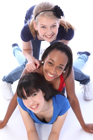 kneeling woman: Playful fun by three multi cultural teenage school student friends made up of mixed race african american, oriental Japanese and caucasian all with big smiles having a laugh. Stock Photo