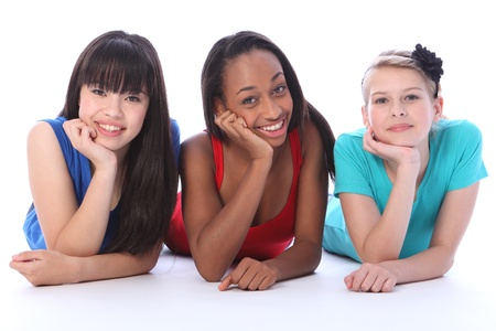 Teenage school student best friends lying on the floor together made up of mixed race african american, oriental Japanese and caucasian all with happy smiles having a laugh. photo