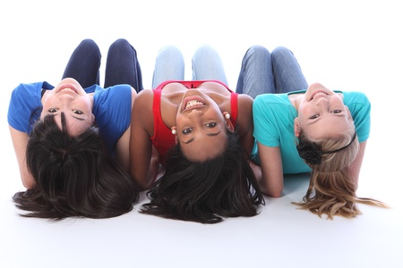 Teenage school student best friends lying on the floor looking backwards together made up of mixed race african american, oriental Japanese and caucasian all with happy smiles having a laugh. Stock Photo - 10782762