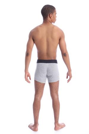 hombre desnudo: Apuesto joven mans mestizos cuerpo en forma saludable tono de detrás de usar ropa interior color gris único jinete. Foto de archivo