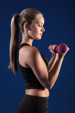black bra: Beautiful young caucasian fitness woman working out with hand weights, doing bicep curl wearing black sports bra with brown hair in long pony tail. Stock Photo