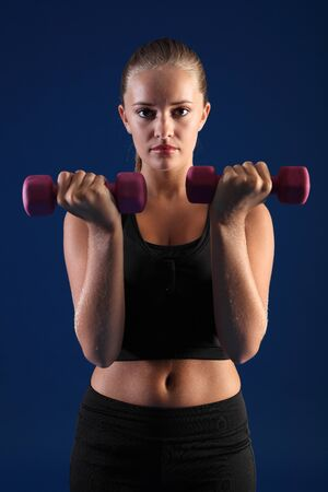 hand bra: Anaerobic exercise by beautiful young caucasian fitness woman using hand weights for bicep curls wearing black sports bra.