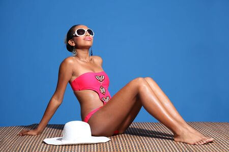 monokini: Long legged young african american woman wearing pink monokini swimsuit sitting on bamboo mat sun tanning with head back and eyes closed. Sun hat and sunglasses nearby.