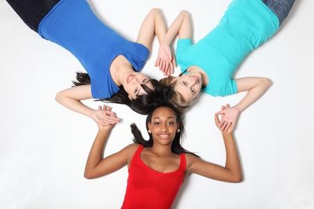 school teens: Golpeteo estrella diversi�n mestizos americanos africanos, orientales japonesas y rubia cauc�sica adolescentes de la escuela amigas estudiante tendido en el suelo mirando hacia arriba con una gran sonrisa.