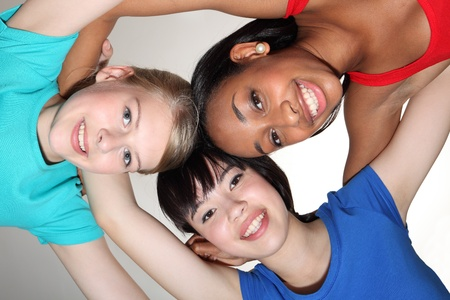Big smiles in fun team group huddle by mixed race african american, oriental Japanese and blonde caucasian teenage school student girl friends looking down to camera. Stock Photo - 10819703