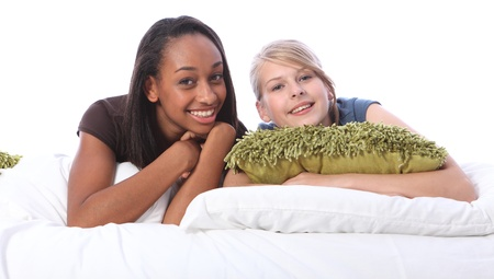 sleepover: Black and white teenage girl friends slumber party. Mixed race african american and blonde caucasian school mates in pyjamas lying on bed.