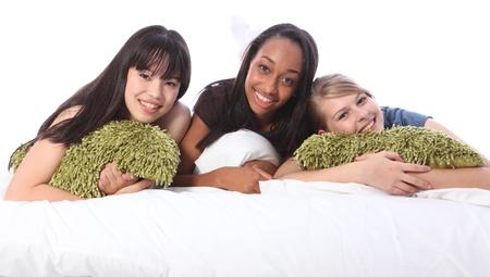 Fiesta de pijamas de tres amigas adolescentes, un mestizo americano africano, oriental compa�eros cauc�sicos y japoneses rubia escuela en pijama acostado en la cama. Foto de archivo - 10819686