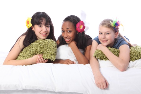 sleepover: Slumber party for three teenage girl friends, a mixed race african american, oriental Japanese and blonde caucasian school mates all wearing flower or feather hair accessories.  Stock Photo