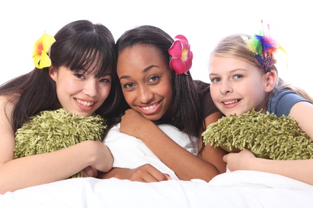 Slumber party for three teenage girl friends, a mixed race african american, oriental Japanese and blonde caucasian school mates all wearing flower or feather hair accessories.  photo