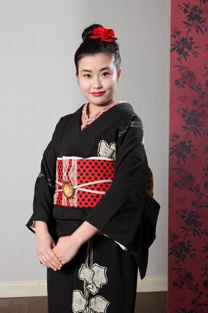 kanzashi: Beautiful young oriental woman wearing black Japanese traditional kimono, a full length robe garment complete with obi sash. Model wearing red kanzashi flower in hair.