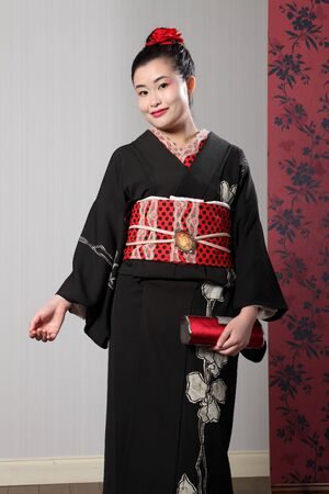 kanzashi: Beautiful young oriental woman wearing black Japanese traditional kimono, a full length robe garment complete with obi sash, a red satin fashion purse and red kanzashi flower in hair.