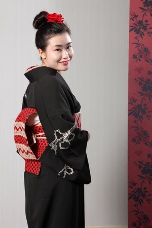 kanzashi: Back view of traditional Japanese kimono worn by beautiful young oriental Asian model woman, complete with obi sash and red kanzashi flower in hair. Stock Photo