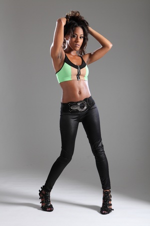 Stunning young african american woman in black leggings and high heels and green top, in a sexy pose in studio, holding up her long dark brown hair. photo