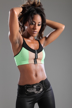 abdomen plano: Retrato de joven impresionante mujer afroamericana modelo de moda en la parte superior del verde, que atacan a una pose sexy sosteniendo su cabello largo de color marrón oscuro.