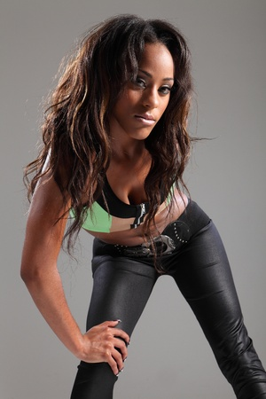 Sulky and stunning young african american fashion model woman in green crop top, skin tight leggings strikes a sexy pose bending over with her long dark brown hair. photo