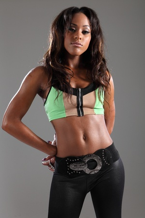 dark brown hair: Provocative and stunning portrait of young african american fashion model woman in green crop top, strikes a sexy moody pose with her long dark brown hair. Stock Photo