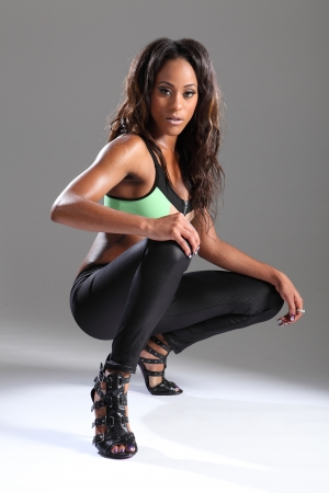 Sexy leggy pose by young african american fashion model woman in green crop top, leggings and showing off black and purple stilettos crouching on the floor. photo