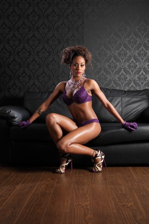 black women naked: Stunning body of young african american glamour model woman wearing sexy purple lace lingerie and leather gloves, on black leather sofa.