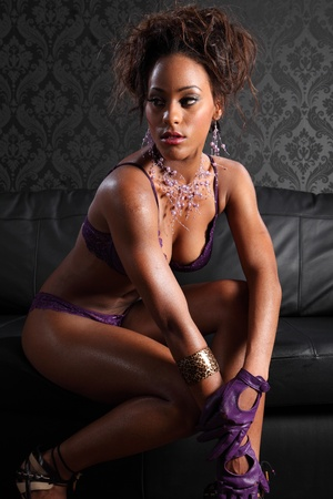 Sexy young african american glamour model woman wearing purple lace lingerie and leather gloves, sitting on black leather sofa. Model has fashion necklace and bracelet on. photo