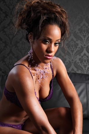 pout: Beautiful young african american glamour model woman wearing purple lace lingerie and leather gloves, showing sexy cleavage. Model has her hair up and wearing a fashion necklace.
