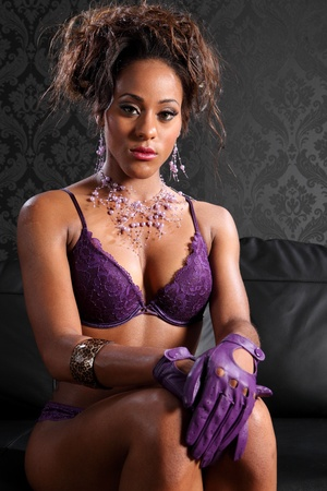Stunning young african american glamour model woman wearing sexy purple lace lingerie and leather gloves, sitting on black leather sofa. Model has fashion necklace and bracelet on. photo