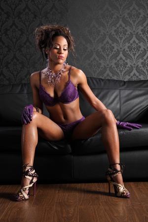 mujeres negras desnudas: Imponente cuerpo de la joven mujer afroamericana modelo de glamour vistiendo guantes de encaje morado lencer�a y ropa de cuero, en el sof� de cuero negro en una pose sexy piernas largas. Foto de archivo