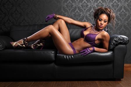 mujeres negras desnudas: Cuerpo sexy de hermosas jóvenes glamour afroamericanos modelo mujer con guantes de lencería y cuero de encaje color púrpura, tumbado en el sofá de cuero negro con tacones de aguja asesinas. Foto de archivo