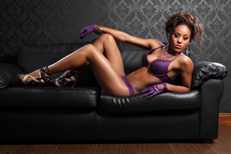naked african: Sexy body of beautiful young african american glamour model woman wearing purple lace lingerie and leather gloves, lying on black leather sofa with killer stiletto heels.